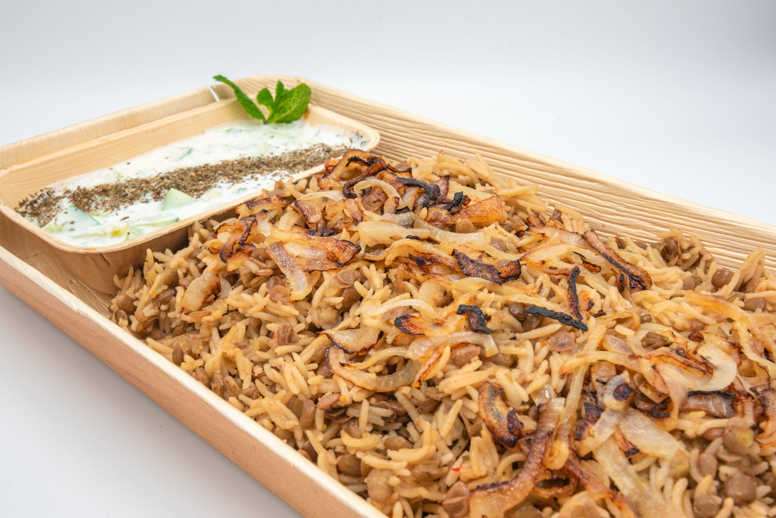 Mujeddara - Traditionelles Reis-Linsengericht mit gerösteten Zwiebeln, dazu Joghurt und eingelegtes Gemüse.